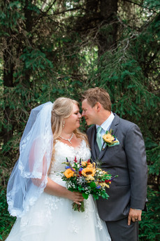 Bride and groom about to kiss, standing in a garden with trees behind them.