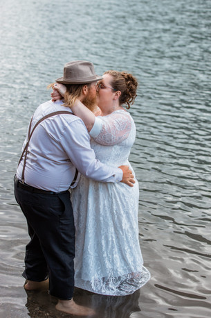 Bride and groom kissing while standing in the water.