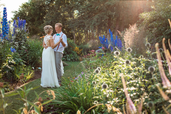 bride and groom dancing among the tall flowers and the sunlight is coming through the trees.