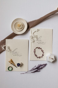 Custom his and her vow booklets flat lay also showing wedding rings.