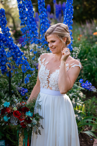 bride standing in the flower garden, you can see the top of her dress with it's intricate lace and her wedding rings.