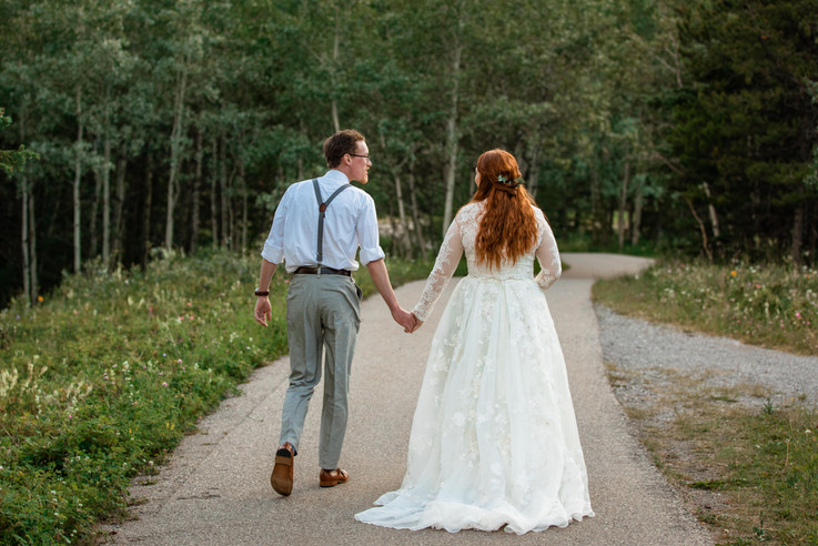Bride and groom walking hand in hand down a tree lined path.