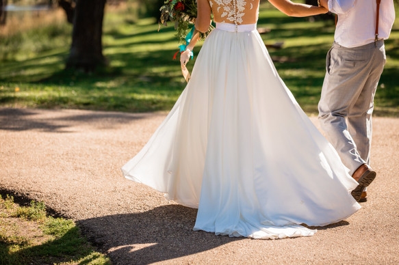 showing the  bottom of the brides dress, how it flows on the road. Walking hand in hand down a road.