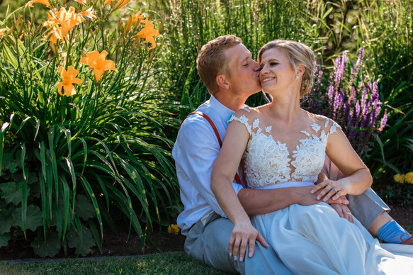 groom is sitting behind the bride giving her a kiss on the cheek.