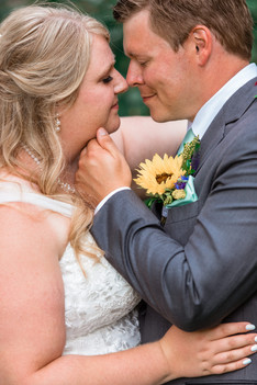 Groom is touching his brides chin and they are embracing.