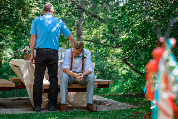 Father of the groom placing his hand on his son's back. Son is sitting at a picnic table.