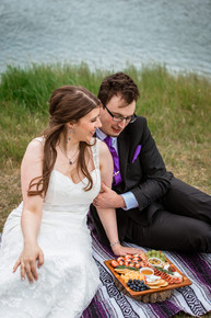 Bride and groom sitting on a blanket at Cascade ponds having a picnic.