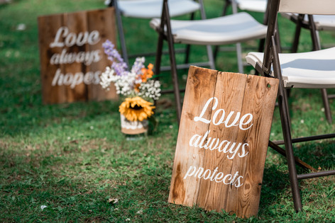 Wooden signs with words at the ceremony. Little vase of flowers.