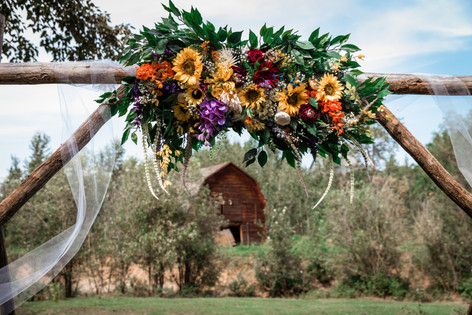 Wedding archway adorned with tule and, flowers and greenery. Little red barn in the distance.
