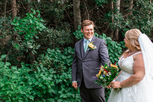 Bride and groom walking in the garden looking at one another smiling.