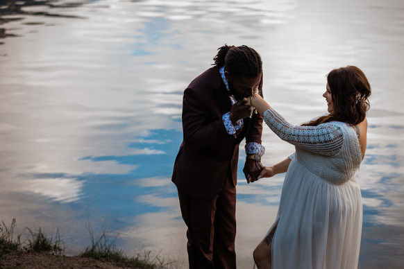 Groom kissing his brides hand while standing beside the water.
