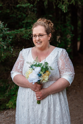 Bride standing alone smiling holding her bouquet.