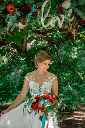 bride looking away holding her colourful bouquet..