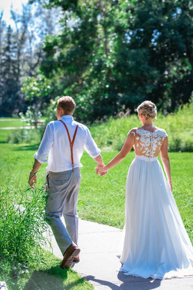 bride and groom walking hand in hand in a beautiful outdoor setting.