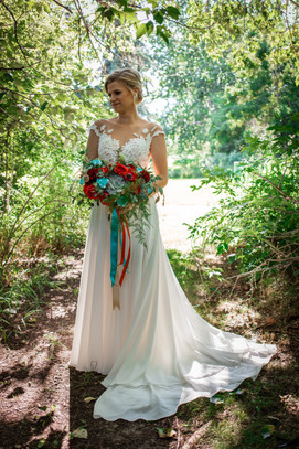 bride standing in the trees showcasing her stunning, vibrant bouquet.