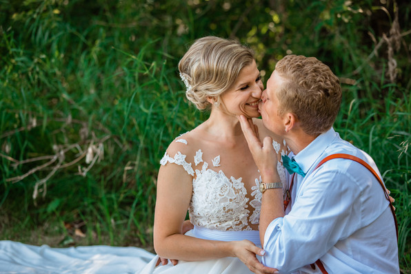 bride and groom sitting on the grass giving a playful kiss.