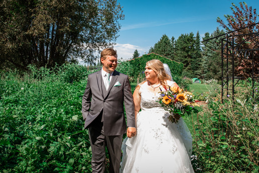Bride and groom walking in a garden, holding hands looking at one another.