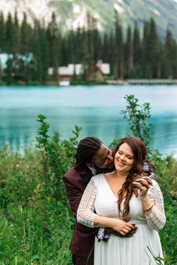 Bride kissing his bride on the cheek from behind in front of Emerald Lake.