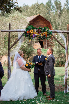 Bride and groom having their ceremony under the archway.