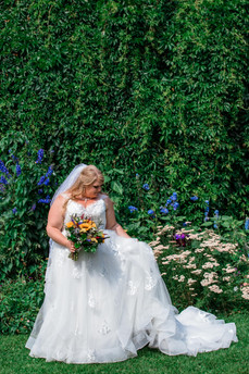 Bride looking to the side fixing her dress. Beautiful flowers and greenery beside her.