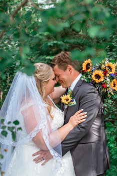 Bride and groom embracing, shown through the trees and all the sunflowers of her bouquet and his boutonniere are shown.