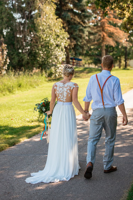 bride and groom walking hand in hand down a road.  Bride is carrying her bouquet.
