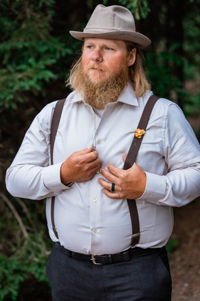 Groom holding with his thumb in his suspender, holding his wedding ring that is on a necklace.