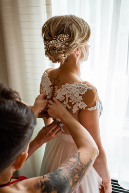 The bride having help button up the back of her dress.