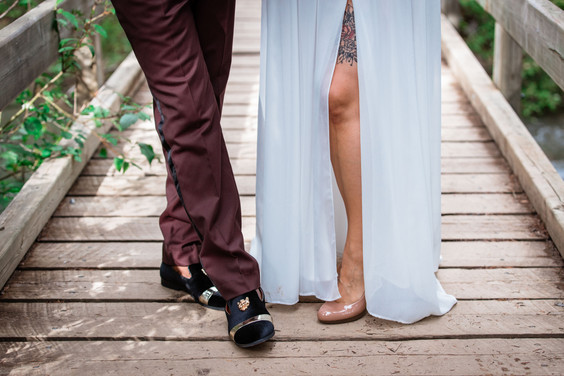 Bride and groom footwear while standing on a wooden bridge.