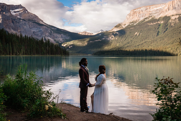 Couple standing in front of Emerald Lake with mountains behind them. The water is calm.