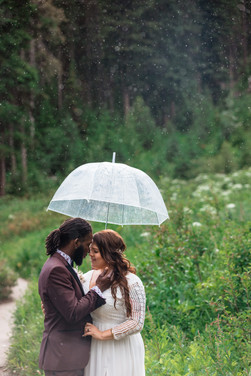 Bride and groom standing closely under a clear umbrella and it is raining.