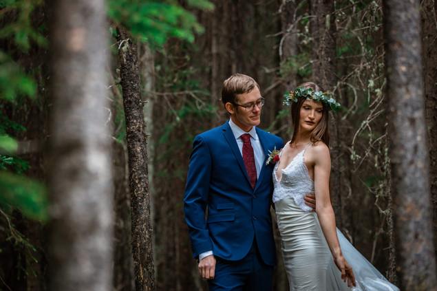 Bride and groom posing in the trees in Kananaskis.