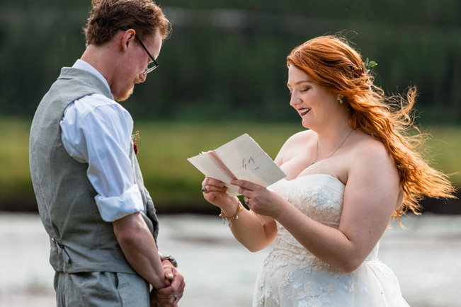 Bride and groom reading from their vow booklet in front of the water.