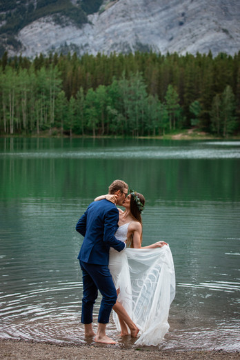 Bride and groom kissing in front of the water in Kananaskis.