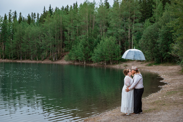 Bride and groom standing under a clear umbrella kissing along the water.