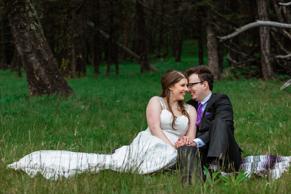 Bride and groom sitting on a blanket looking into each other's eyes