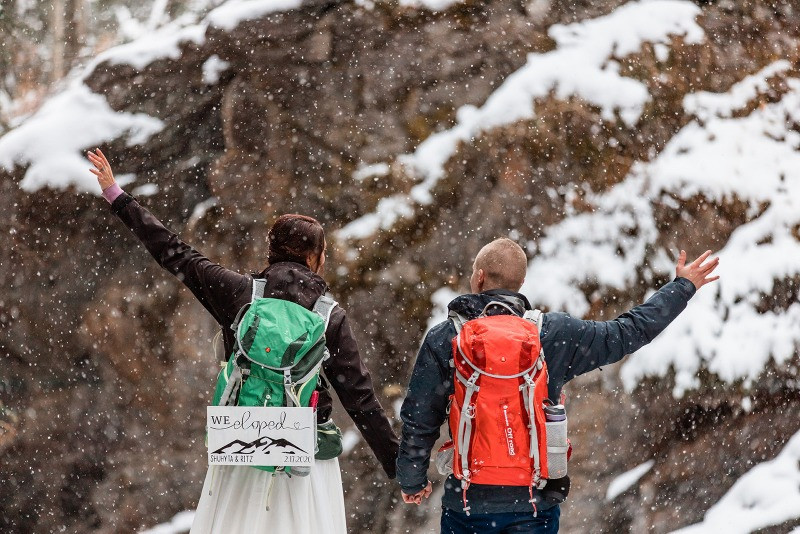 Bride and groom who eloped in the winter, hiking backpacks, we eloped sign ideas