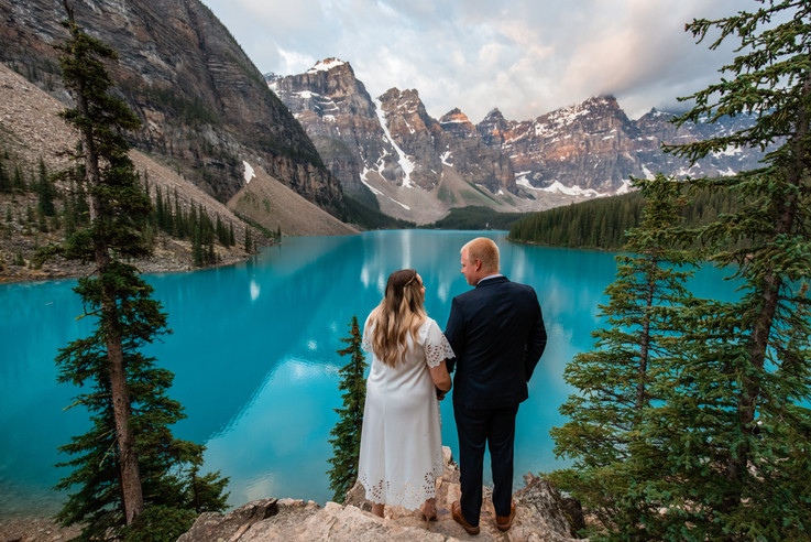 Bride and groom looking at one another standing in front of Moraine Lake and the mountains.
