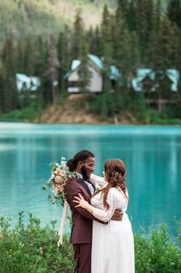 Bride and groom standing in front of one another smiling in front of Emerald Lake.