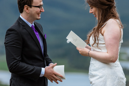 Bride and groom reading personalized wedding vows that are hand written in a booklet. Overlooking Banff National Park.