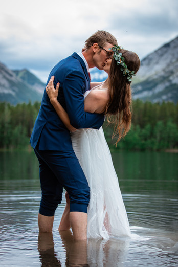 Bride and groom embracing in front of the water in Kananaskis.