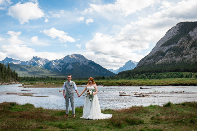 Bride and groom holding hands in front of the water with mountains in the background.