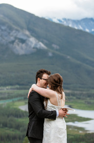 Bride and groom holding each other at a lookout point overlooking Banff National Park.