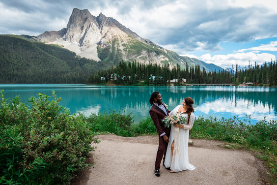 Bride and groom standing in front of Emerald Lake and a mountain.