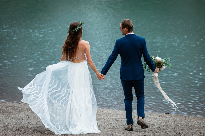 Bride and groom posing in front of the water in Kananaskis. Couple is looking at the water and the brides dress in flowing in the wind.
