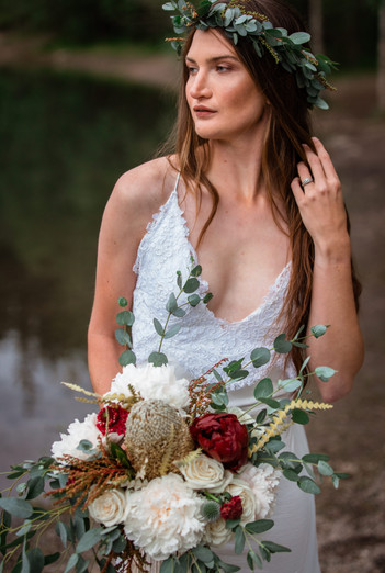 Bride standing in front of the water holding her bouquet.
