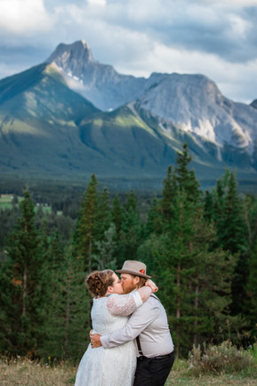 Bride and groom standing together kissing with the trees and mountains behind them.