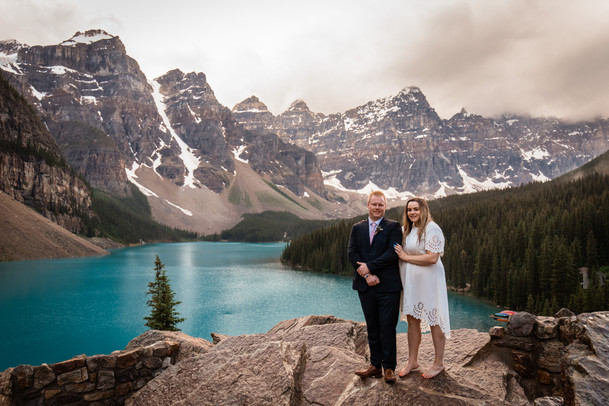 Couple standing on the rocks overlooking Moraine Lake and the mountains.