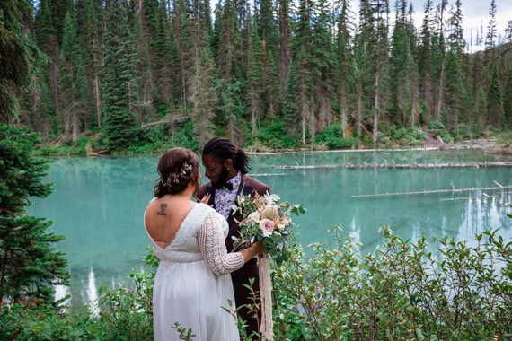 Bride and groom during their first look with Emerald Lake in the background. Showing the back of her dress and bouquet.