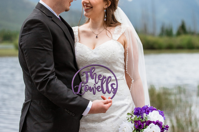 Bride and groom showing their wooden sign of their new chosen last name in front of the water